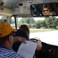 Program Consultant John Wyatt monitors Amber Brown as she navigates the course during the driver trainer instructor training at Franklin County High School. Brown has been driving a bus for three years after her aunt, a bus driver in Boone County, encouraged her to give it a try.  Photo by Amy Wallot, July 9, 2014